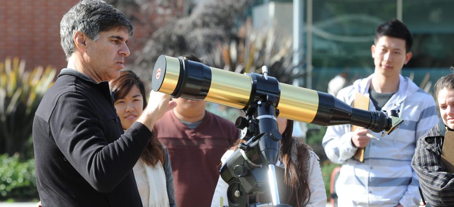 Professor and students surrounding a telescope
