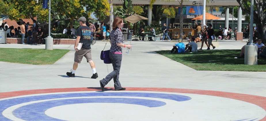 Students walking by the OCC Logo