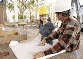 Two architects wearing hard hats discuss a design at a construction site
