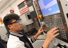 Male student in safety goggles presses buttons to program a machine